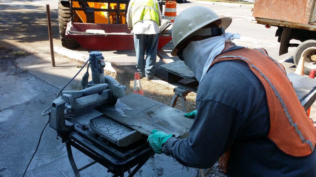 J. D. Miles & Sons employee cutting slate tiles